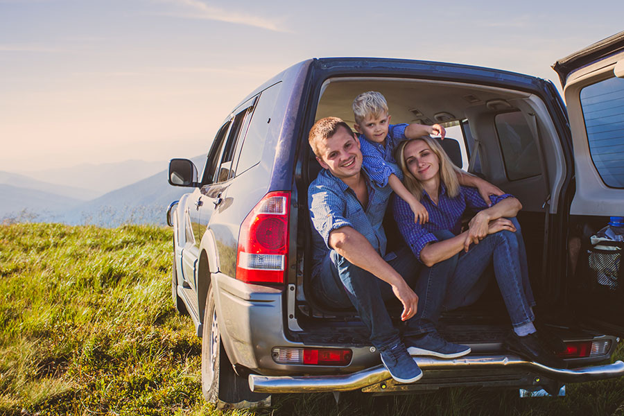 Blog - Young Parents With Son Sitting In Open Trunk Of Jeep In The Mountains